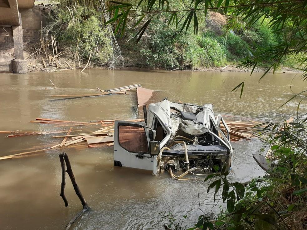 Caminhão carregado com madeira cai no Rio Peixe e deixa motorista ferido
